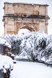 Un giorno adorabile di neve a Roma, l'Italia, il 26 febbraio 2018: una bella vista dell'arco di Tito vicino al Colosseum sotto la immagine stock