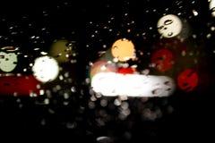 Un giorno di notte della pioggia di Bokeh con le gocce di pioggia Immagine Stock