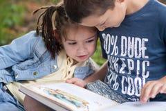Un giorno soleggiato una bambina con le trecce in una giacca blu e Fotografie Stock
