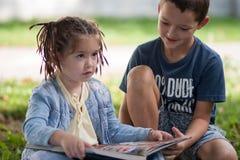 Un giorno soleggiato una bambina con le trecce in una giacca blu e Fotografie Stock Libere da Diritti