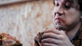 Un giovane è brutto e maleducato mangiante i panini Mangia gli alimenti a rapida preparazione Il concetto della società di obesit stock footage