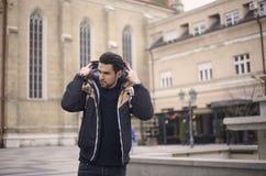 un giovane, all'aperto, mettente maglia con cappuccio del cappuccio sulla testa immagini stock libere da diritti