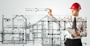 Un giovane architetto che disegna una pianta della casa Fotografie Stock Libere da Diritti