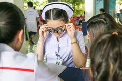 Un giovane asiatico cura fare la prova della visione facendo uso della prova ottica franco Fotografia Stock