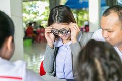 Un giovane asiatico cura fare la prova della visione facendo uso della prova ottica franco Immagini Stock