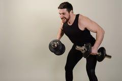 Un giovane atleta si esercita con le teste di legno sullo sviluppo dei muscoli delle spalle fotografia stock