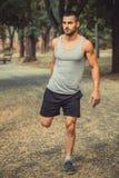 Un giovane, atleta sviluppato si prepara nel parco Immagine Stock