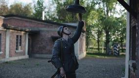 Un giovane attore maschio vestito come soldato tedesco sta fingendo di cambiare una lampadina in una lanterna che appende sopra u video d archivio