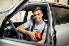 Un giovane attraente sta sedendosi in un'automobile che è riparata da lui fotografia stock