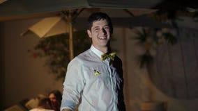 Un giovane bagna in camicia ed altri vestiti nello stagno Partito alla notte in una villa tropicale Bagno ubriaco stock footage