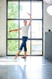 Un giovane ballerino di balletto maschio bello che pratica in uno stile A del sottotetto immagine stock