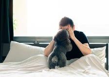Un giovane barboncino nero adorabile che bacia il proprietario cui ritenga triste e serio sul letto dopo per svegliare di mattina fotografia stock