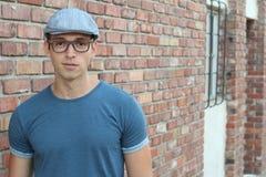 Un giovane bello in vestiti normali che indossano cappello ed i vetri con lo spazio della copia Fotografia Stock Libera da Diritti