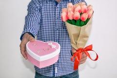 Un giovane in camicia e jeans di plaid blu, danti un mazzo dei tulipani e di un contenitore di regalo in forma di cuore, su un fo fotografie stock