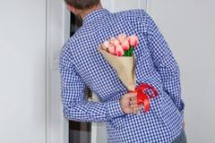 Un giovane in camicia e jeans di plaid blu, tenenti un mazzo dei tulipani dietro il suo indietro e le sbirciate nella porta apert fotografia stock libera da diritti