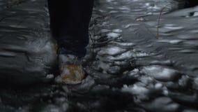 Un giovane cammina attraverso la neve alla notte nel legno archivi video