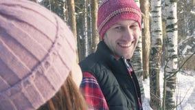 Un giovane cammina con una ragazza nella foresta dell'inverno, un giorno soleggiato archivi video