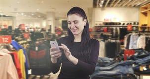 Un giovane castana impressionato sta leggendo un messaggio su un telefono cellulare in un centro commerciale video d archivio