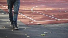 Un giovane che cammina a partire dal campo da giuoco Autumn Time stock footage