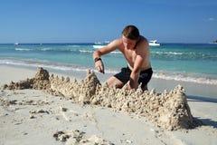 Un giovane che fa il castello della sabbia Fotografia Stock