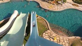 Un giovane che fa scorrere giù all'acquascivolo nel aquapark Vista in prima persona Movimento lento stock footage