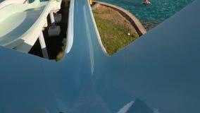 Un giovane che fa scorrere giù all'acquascivolo nel aquapark Vista in prima persona Movimento lento archivi video