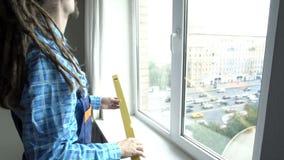Un giovane che misura una finestra stock footage