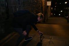 Un giovane che prende le foto sulle vie di Edimburgo alla notte immagine stock