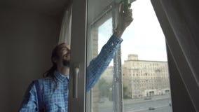 Un giovane che pulisce una finestra stock footage