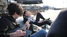 Un giovane che si trova su un banco con i suoi amici e che gioca chitarra all'aperto stock footage