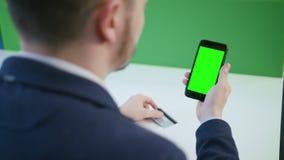 Un giovane che usando Smartphone con uno schermo verde archivi video