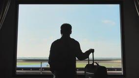 Un giovane con bagaglio guarda l'aeroplano decollare dalla finestra della sua camera di albergo stock footage