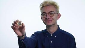 Un giovane con un bitcoin della moneta archivi video