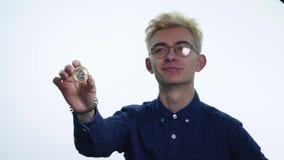 Un giovane con un bitcoin della moneta stock footage