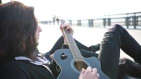 Un giovane con capelli lunghi che giocano chitarra e cantare archivi video