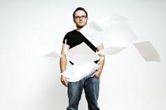 Un giovane con i lotti di lavoro di ufficio. Immagine Stock