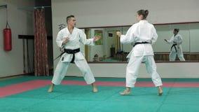 Un giovane con le arti marziali di pratica Goju-Ryu di una donna e di un corpo muscolare Karatè-fa movimento lento eccellente archivi video