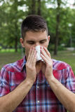 Un giovane con un'allergia che starnutisce nel fazzoletto Fotografie Stock Libere da Diritti