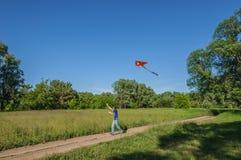Un giovane con un aquilone di volo Fotografie Stock
