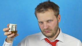 Un giovane con una barba in una camicia ed in un legame bianchi che tengono un vetro di alcool in cui ci sono dollari dei soldi,  stock footage