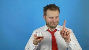 Un giovane con una barba in una camicia ed in un legame bianchi tiene un vetro con l'alcool e rifiuta l'alcool, dipendenza di alc video d archivio