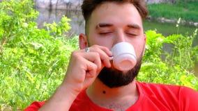 Un giovane con una barba gode di di bere il caffè in natura Primo piano di un tipo brutale con una tazza bianca di tè in sua mano video d archivio