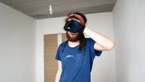 Un giovane con una barba pulisce il sudore dalla sua fronte Ripari il concetto stock footage