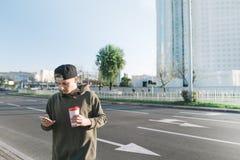 Un giovane con una tazza di caffè in sue mani scrive un messaggio sul suo telefono mentre cammina intorno alla città Sui preceden Fotografia Stock Libera da Diritti