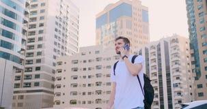 Un giovane con uno zaino che parla sul telefono nei precedenti delle costruzioni stock footage