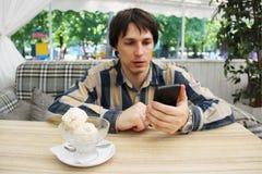 Un giovane conta con uno smartphone il contenuto calorico del gelato la dieta e le domande di aiuto dello smartphone appaiono bel immagine stock