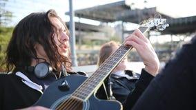 Un giovane in cuffie che giocano chitarra e cantare archivi video