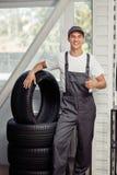 Un giovane e automechanic attraente sta stando vicino a parecchie gomme di automobile al lavoro immagine stock