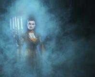 Un giovane e vampiro di signora che tiene le candele Fotografie Stock Libere da Diritti