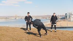 Un giovane ed eseguire i trucchi e le vibrazioni acrobatici sull'erba mentre i suoi amici che lo guardano archivi video